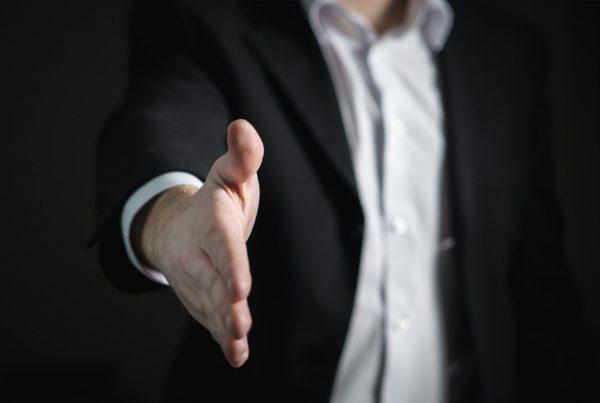 foto muže v černém, který podává pravou ruku
