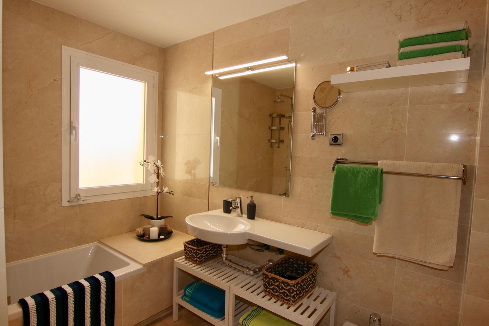 koupelna s vanou a velkým zrcadlem