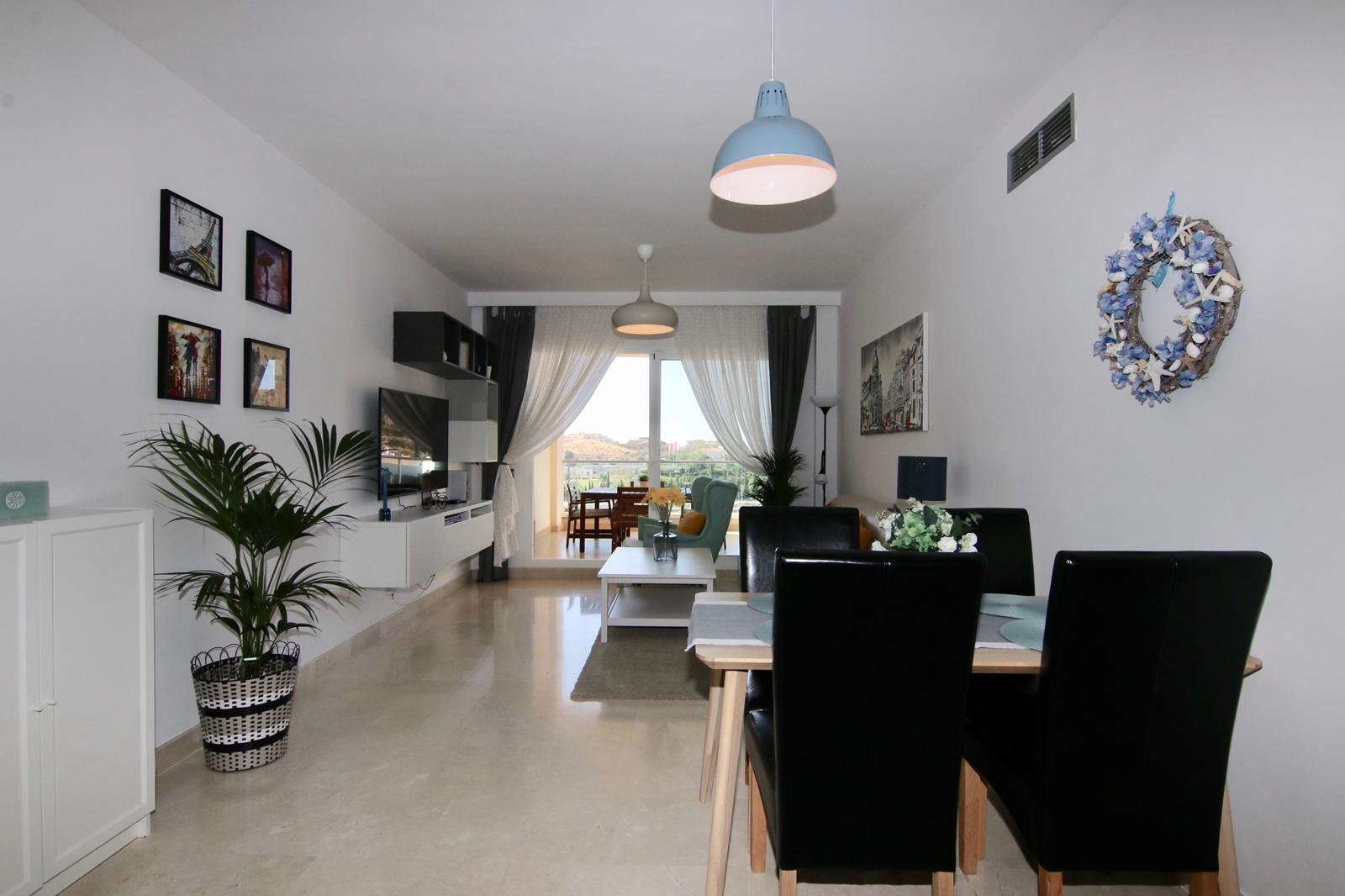 pohled na jídelní kout s jídelním stolem, obývací pokoj s TV, květinou a venkovním balkonem