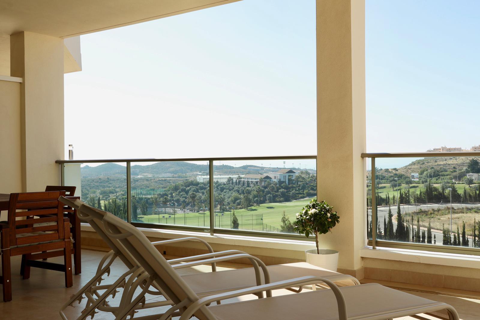 pohled z venkovního balkonu s lehátky na zeleň ve Španělsku