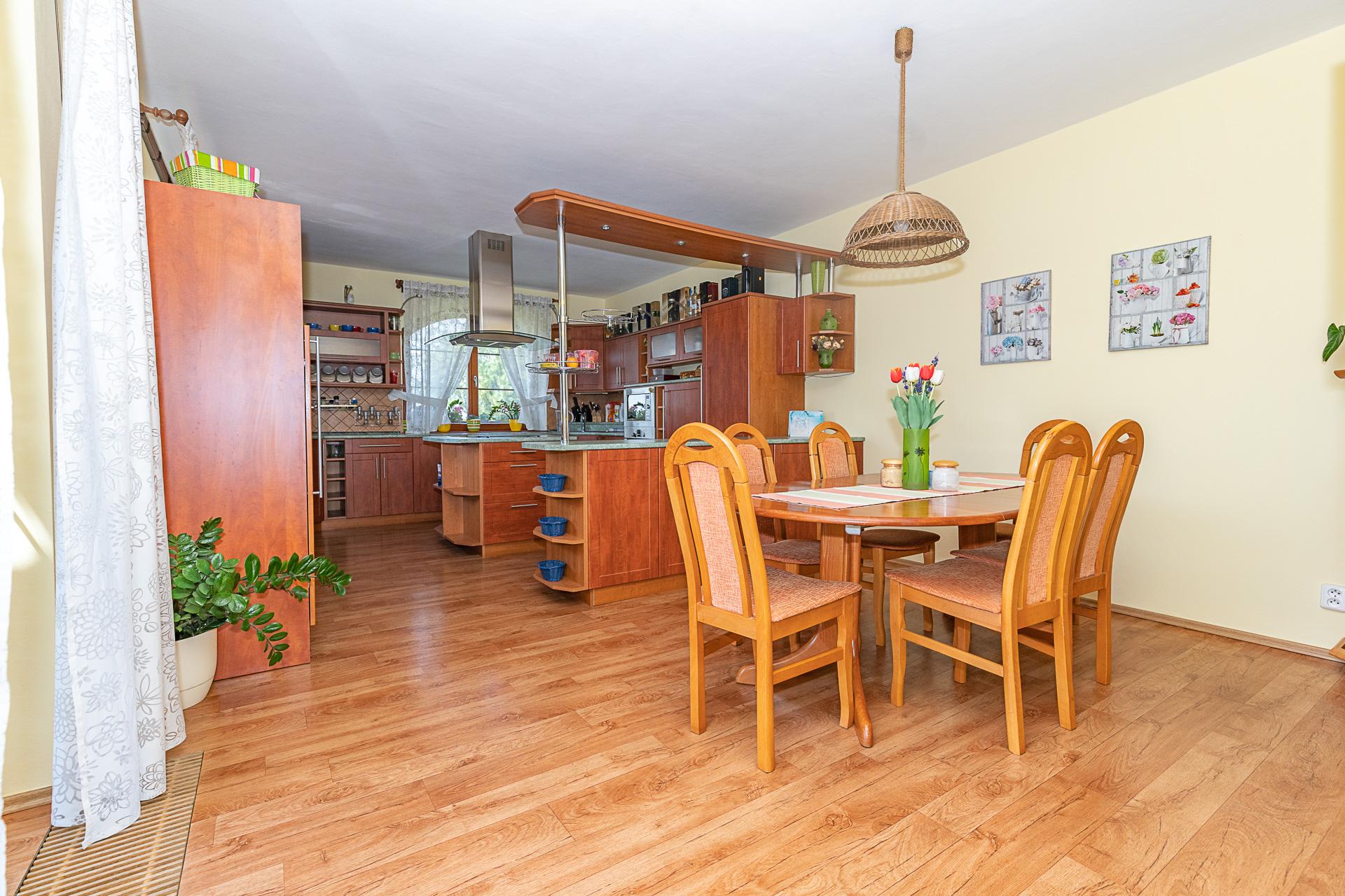 kuchyňský kout s ostrůvkem, okenem a jídelním stolem