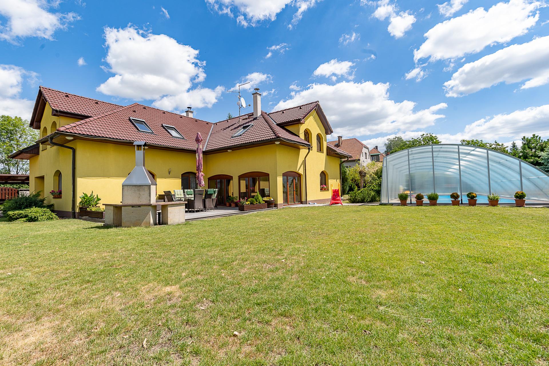 pohled na dům s terasou, bazénem a zahradou