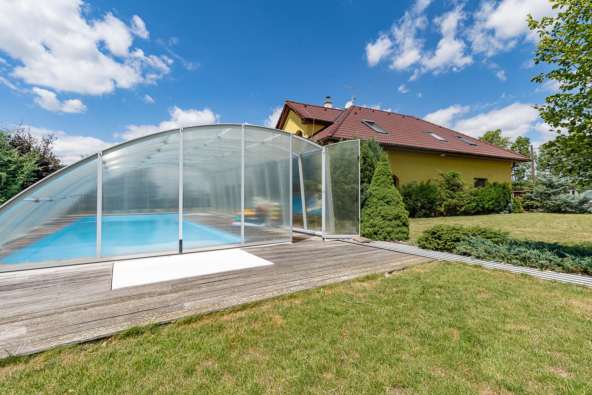 pohled na zastřešený bazén a dům se zahradou