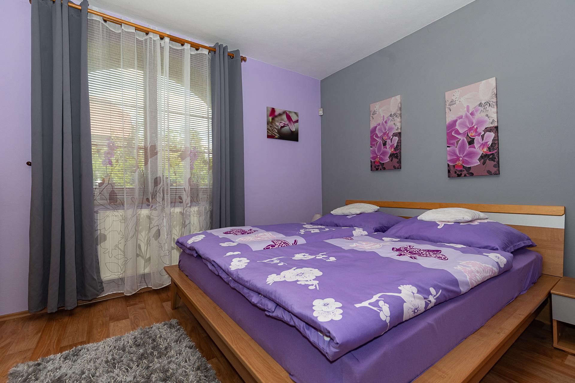 ložnice s dřevěnou postelí, obrazy na stěnách a oknem