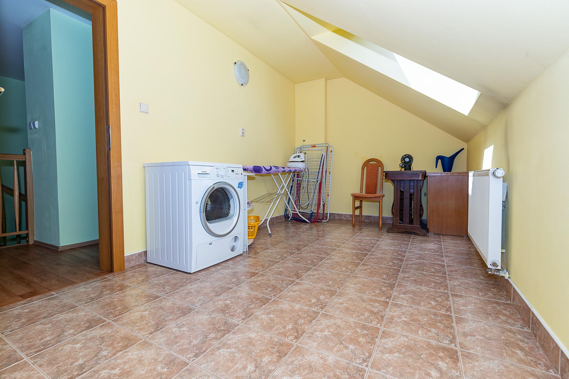 prádelna v horní části domu s pračkou, žehlícím prknem a šicím strojem