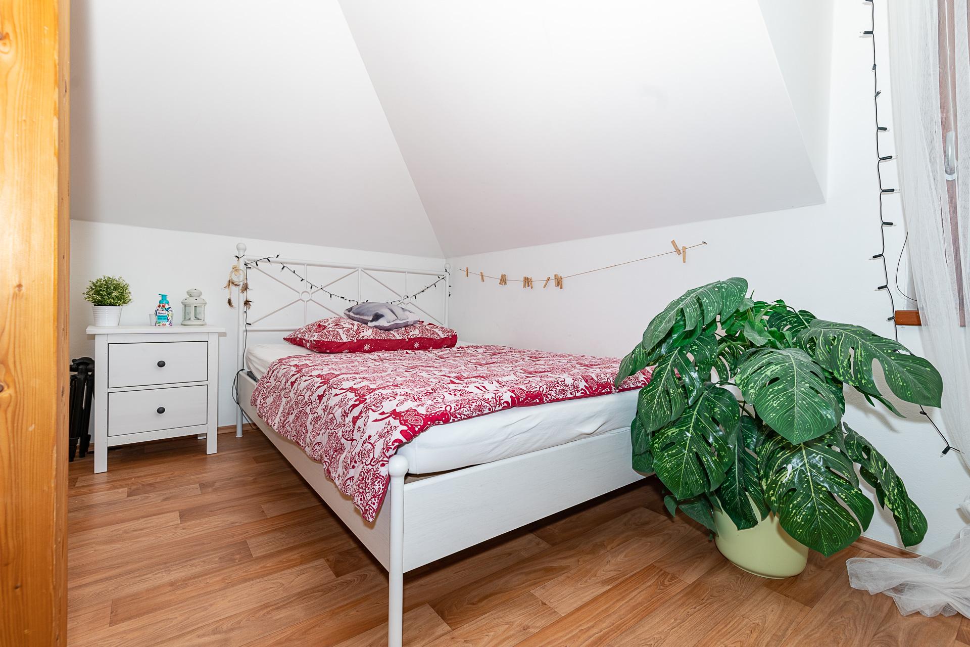 ložnice s bílou postelí a květinou