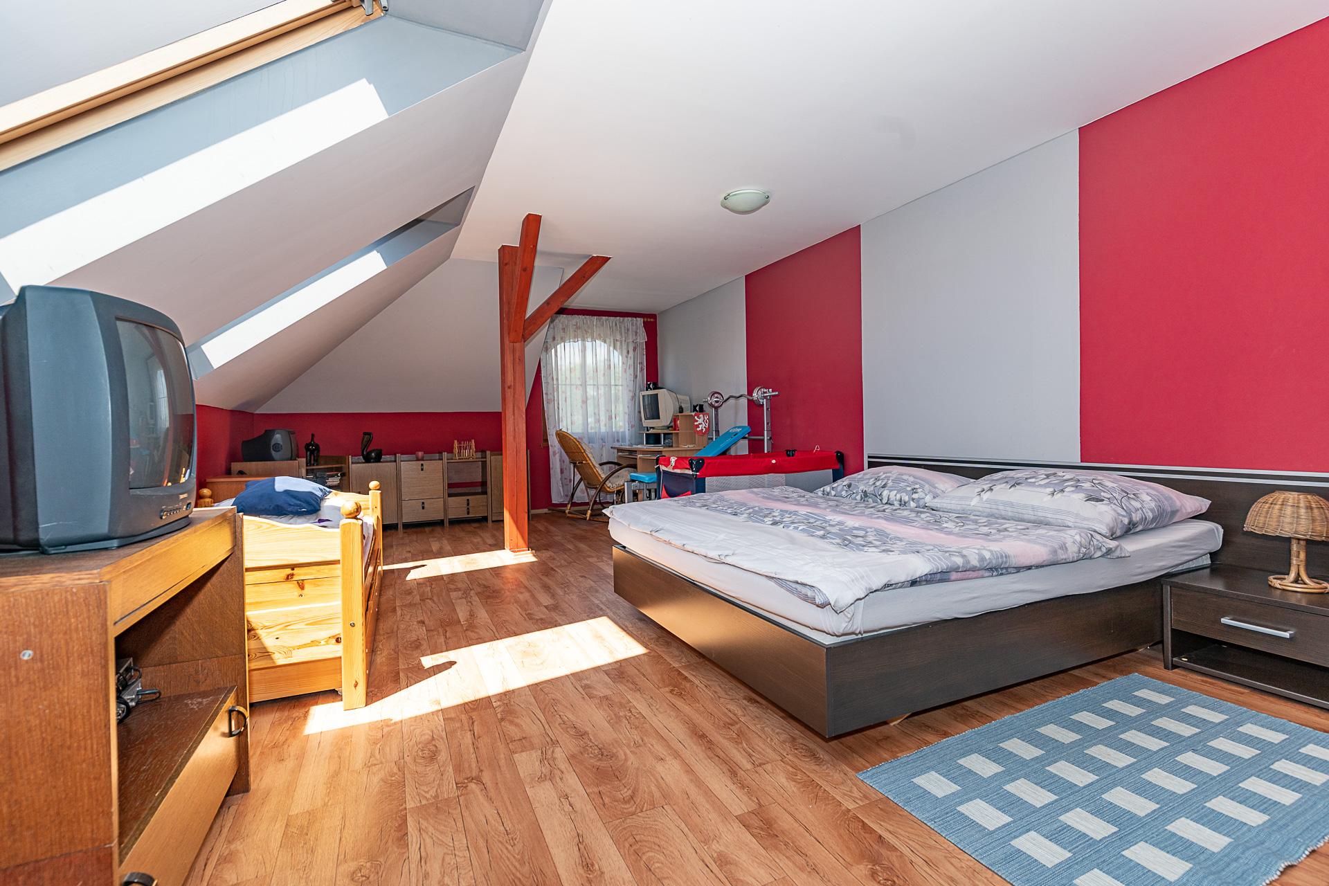 ložnice s postelí, TV, modrým kobercem, pracovním stolem a střešním oknem