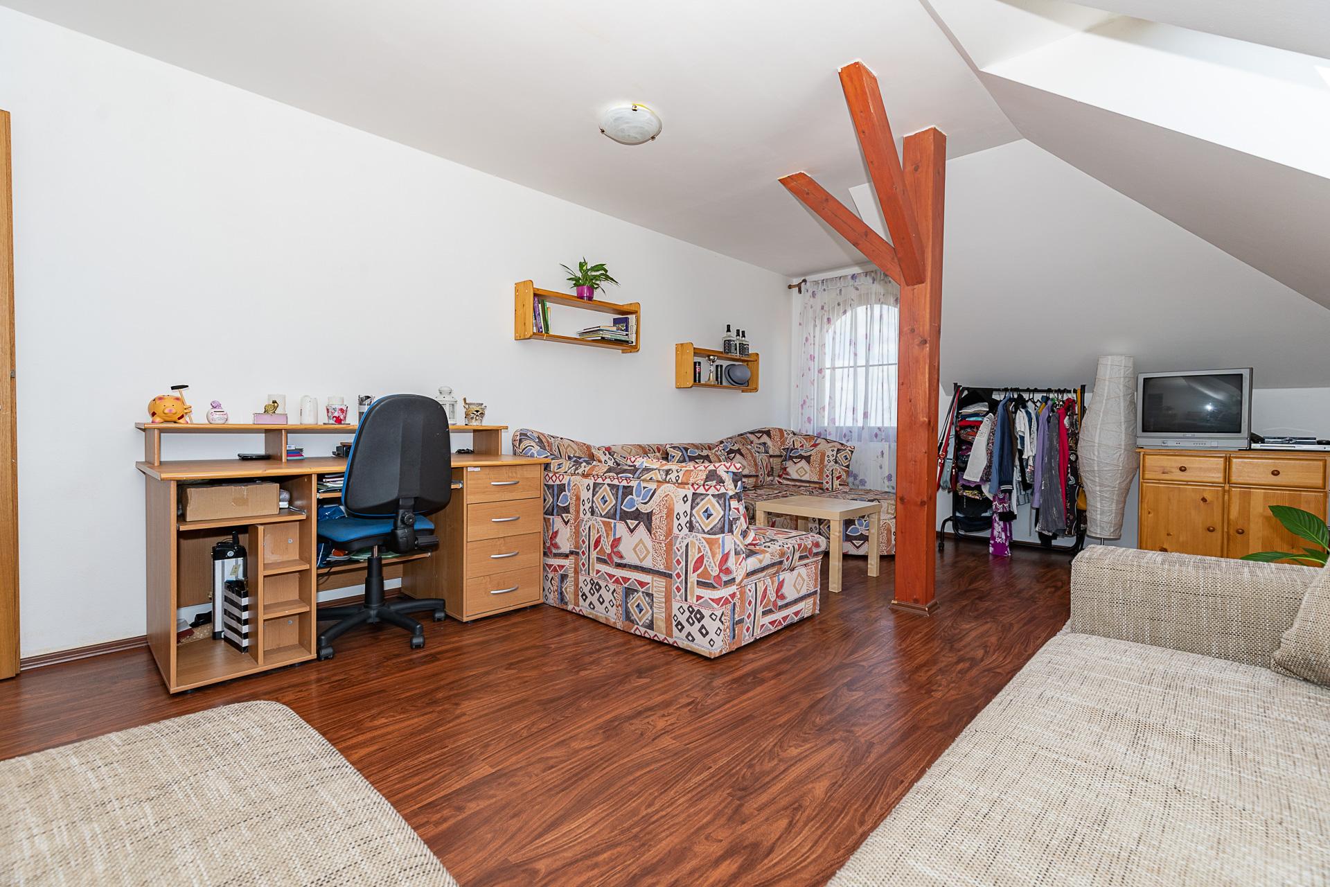 ložnice s trámem ve středu pokoje, pohovkou, TV, a pracovním stolem