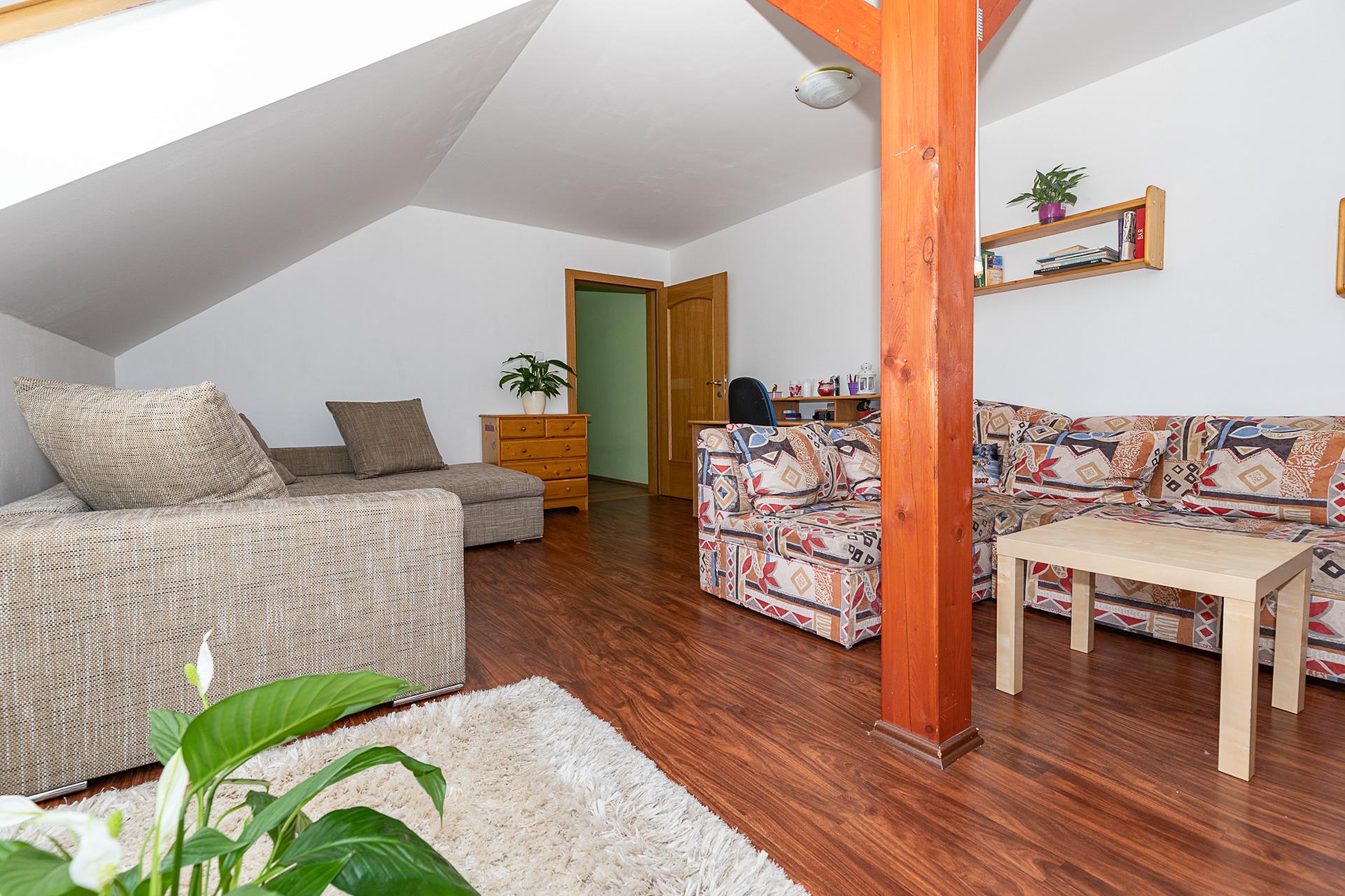 ložnice s trámem ve středu pokoje, pohovkou, bílí koberec