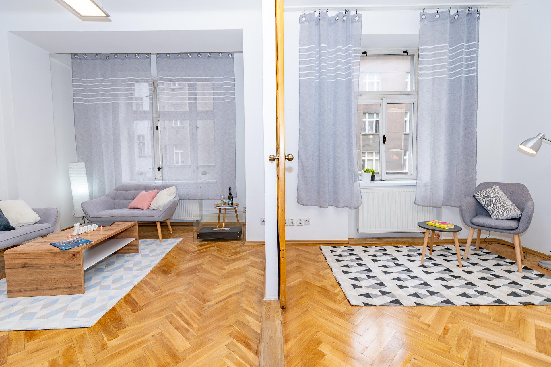 pohled na ložnici a obývací pokoj s dřevěnou podlahou a nábytkem