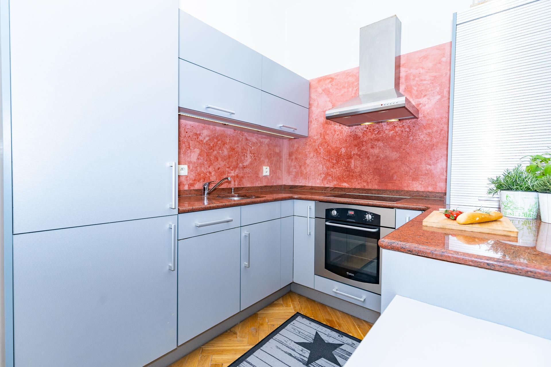 kuchyňský kout v šedé barvě, troubou, digestoří a kobercem
