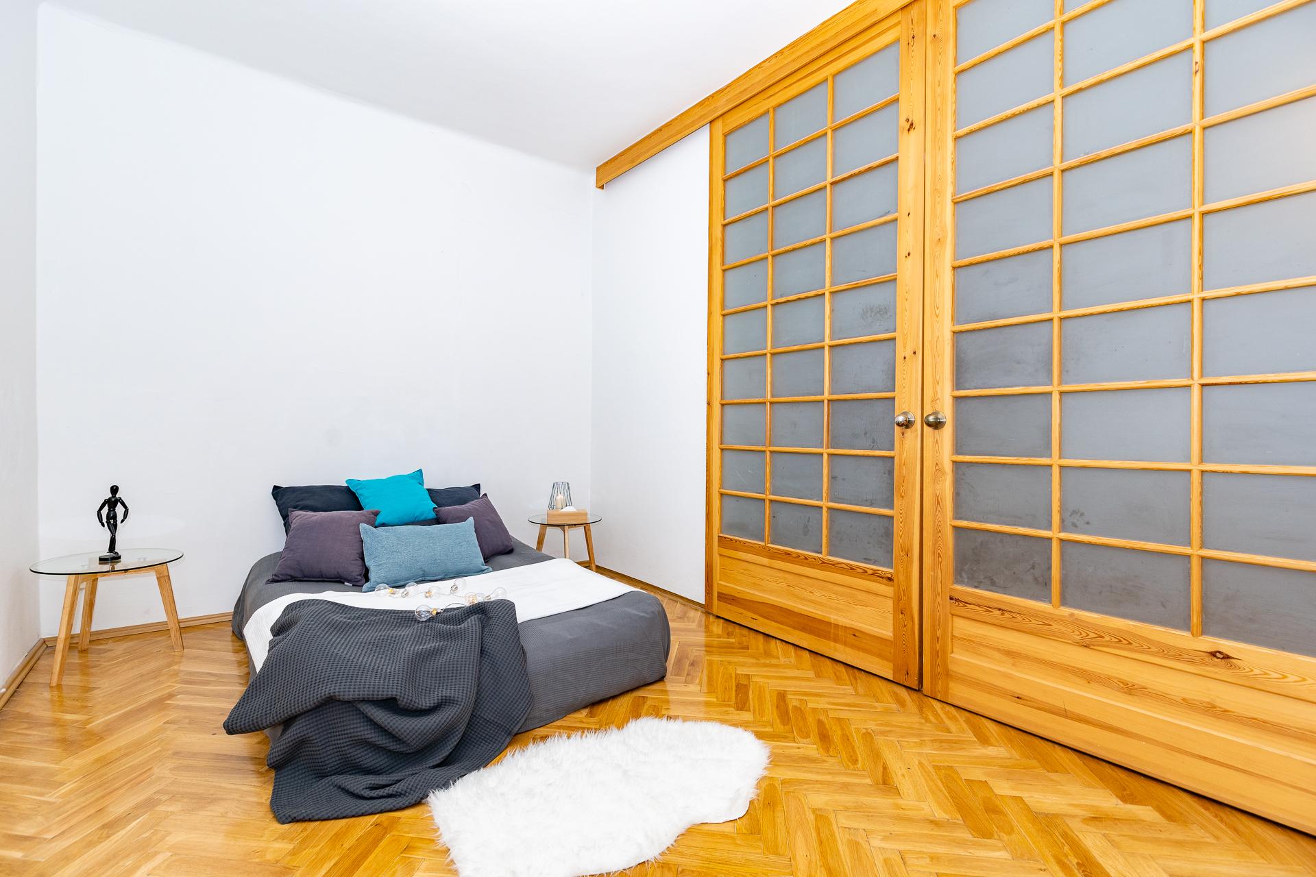 ložnice s postelí a obrovské posuvné dřevěné dveře