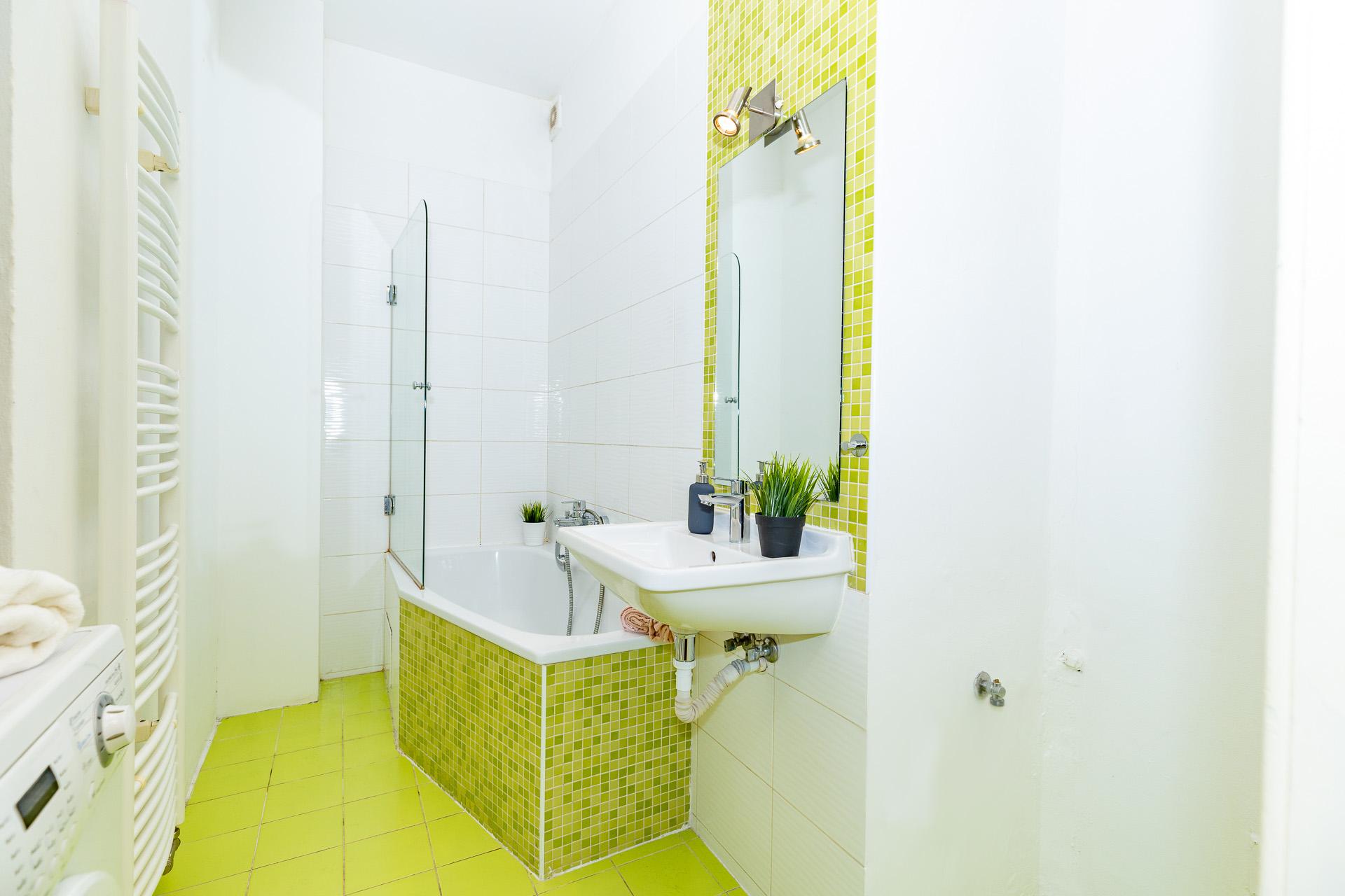 foto koupelny s vanou, umyvadlem, květinou a pračkou