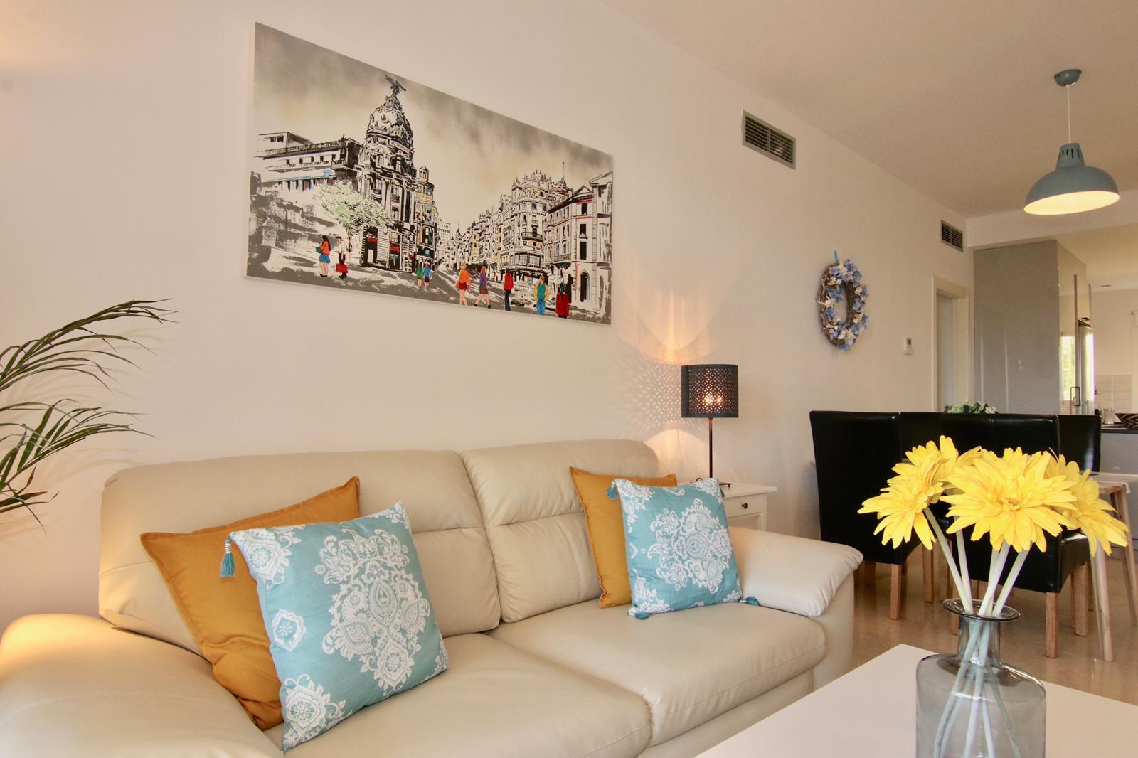 obývací pokoj s gaučem a obrazem na stěně a květinou ve váze na stole