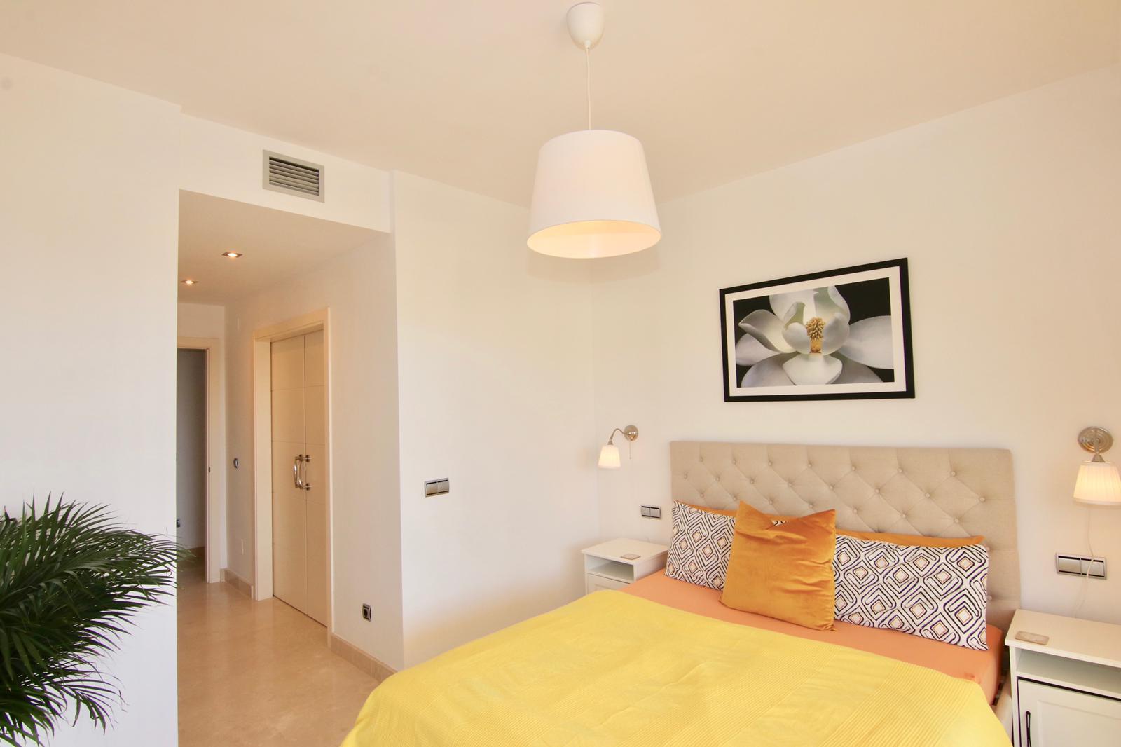 foto ložnice s čalouněnou postelí a obrazem na stěně a stropním světlem