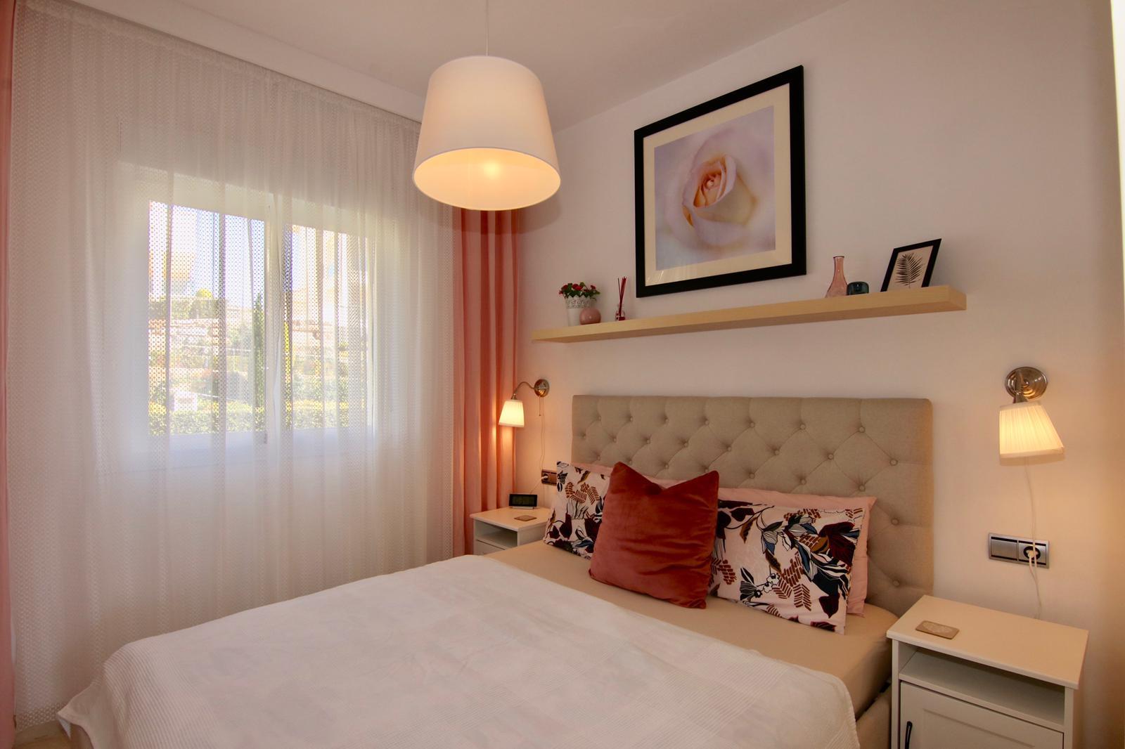 foto ložnice s čalouněnou postelí a obrazem na stěně