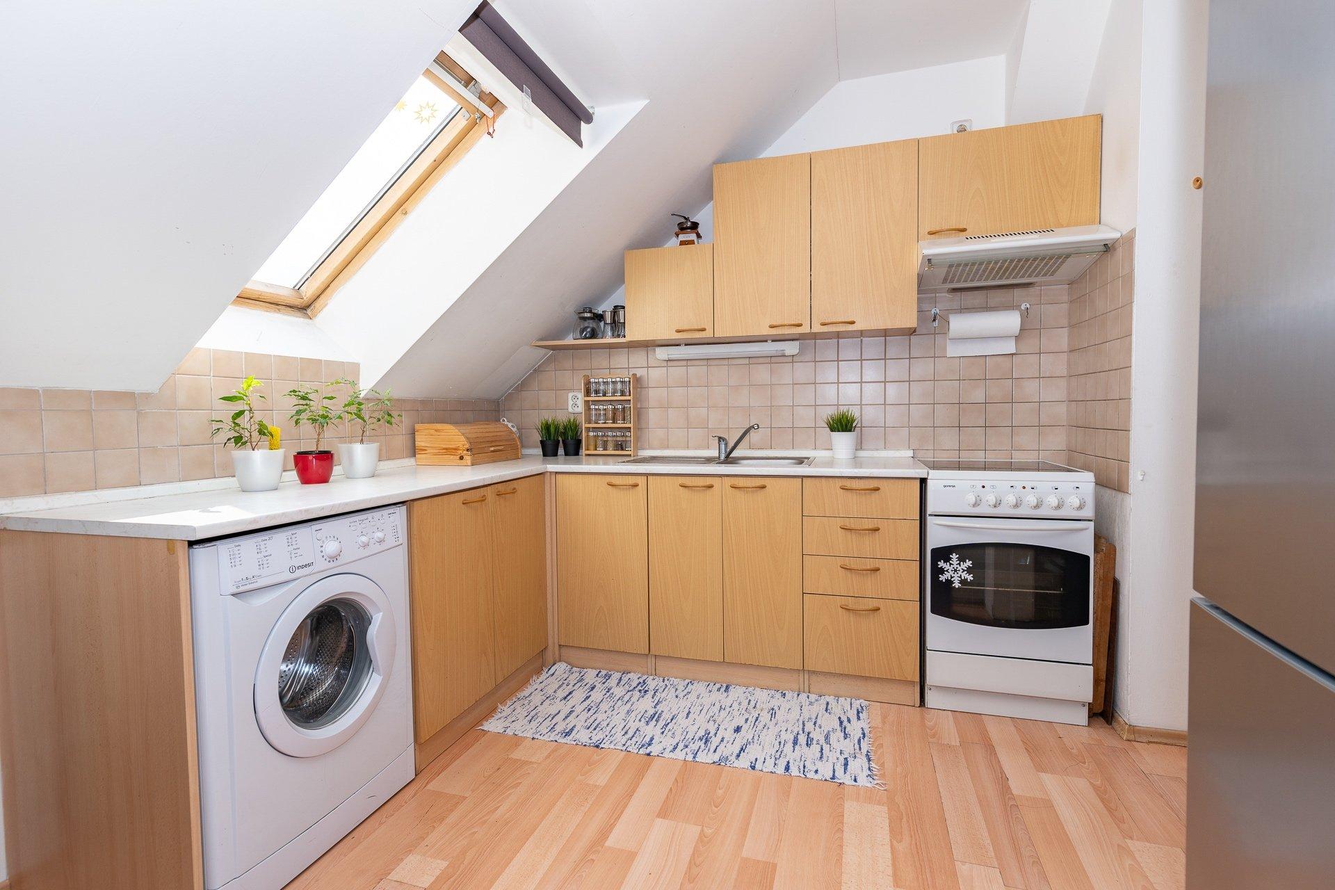 kuchyňský kout s pračkou, troubou se sporákem a střešním oknem
