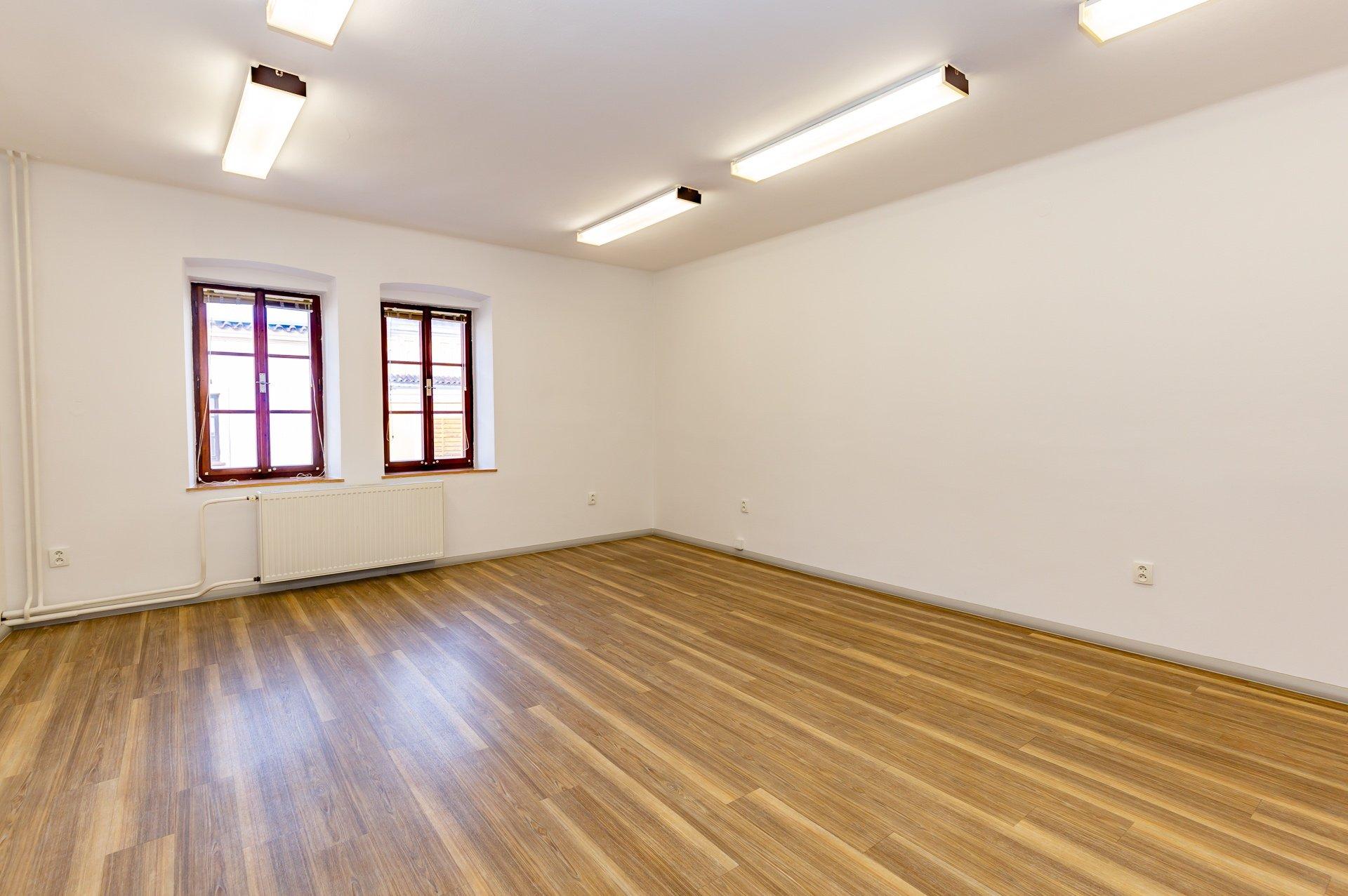 prázdný kancelářský prostor s dřevěnou podlahou a okny