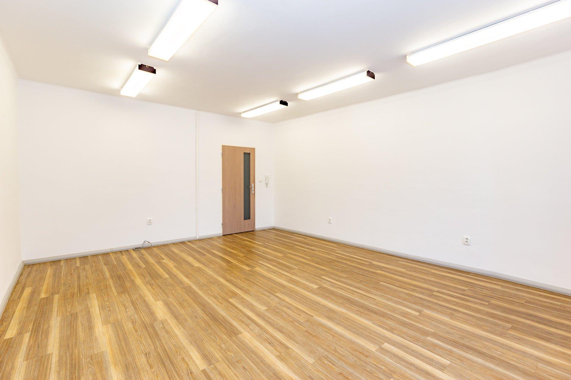 prázdný kancelářský prostor s řevěnou podlahou, stropní zářivky a dveře