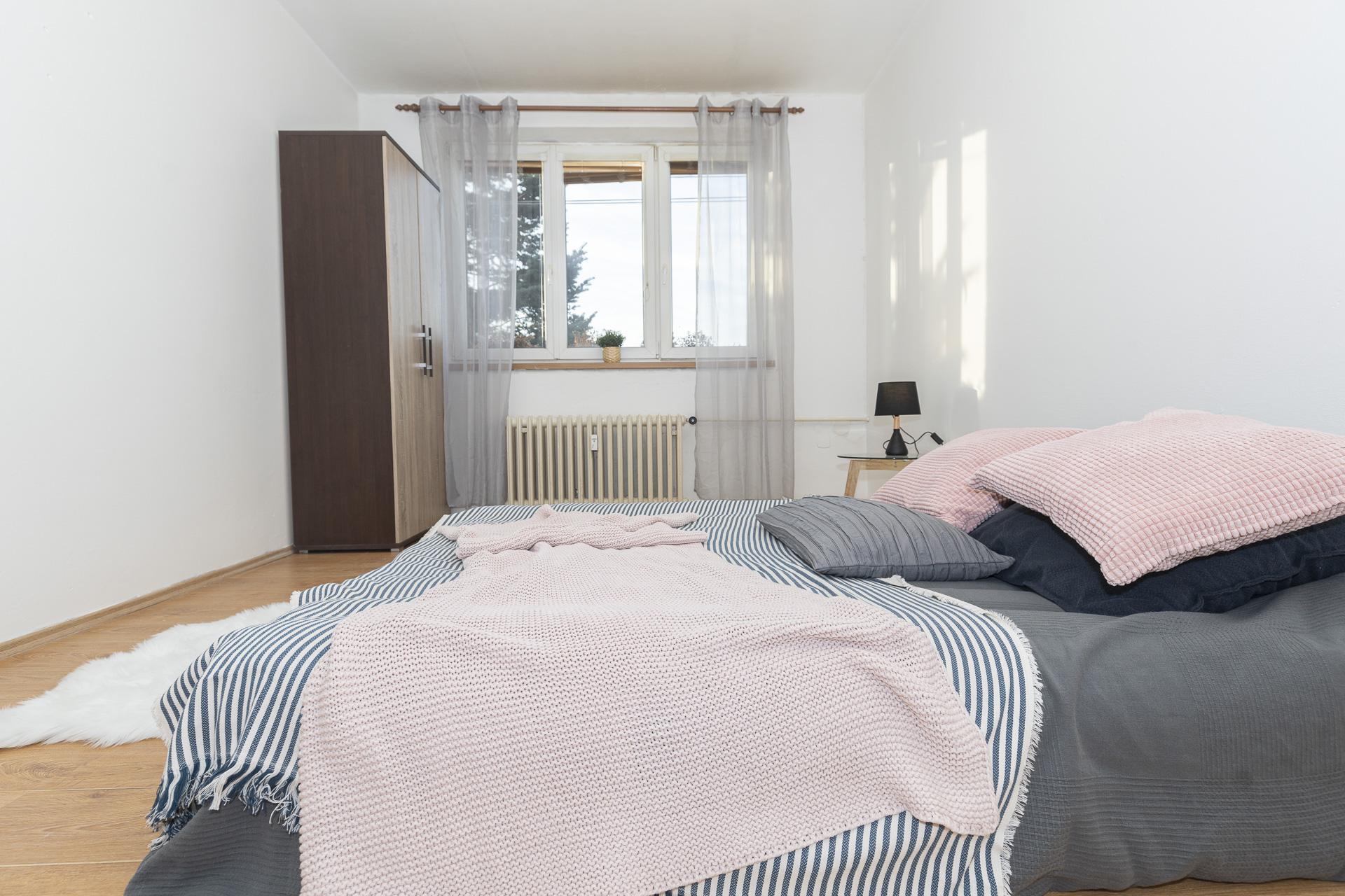 ložnice s postelí a oknem