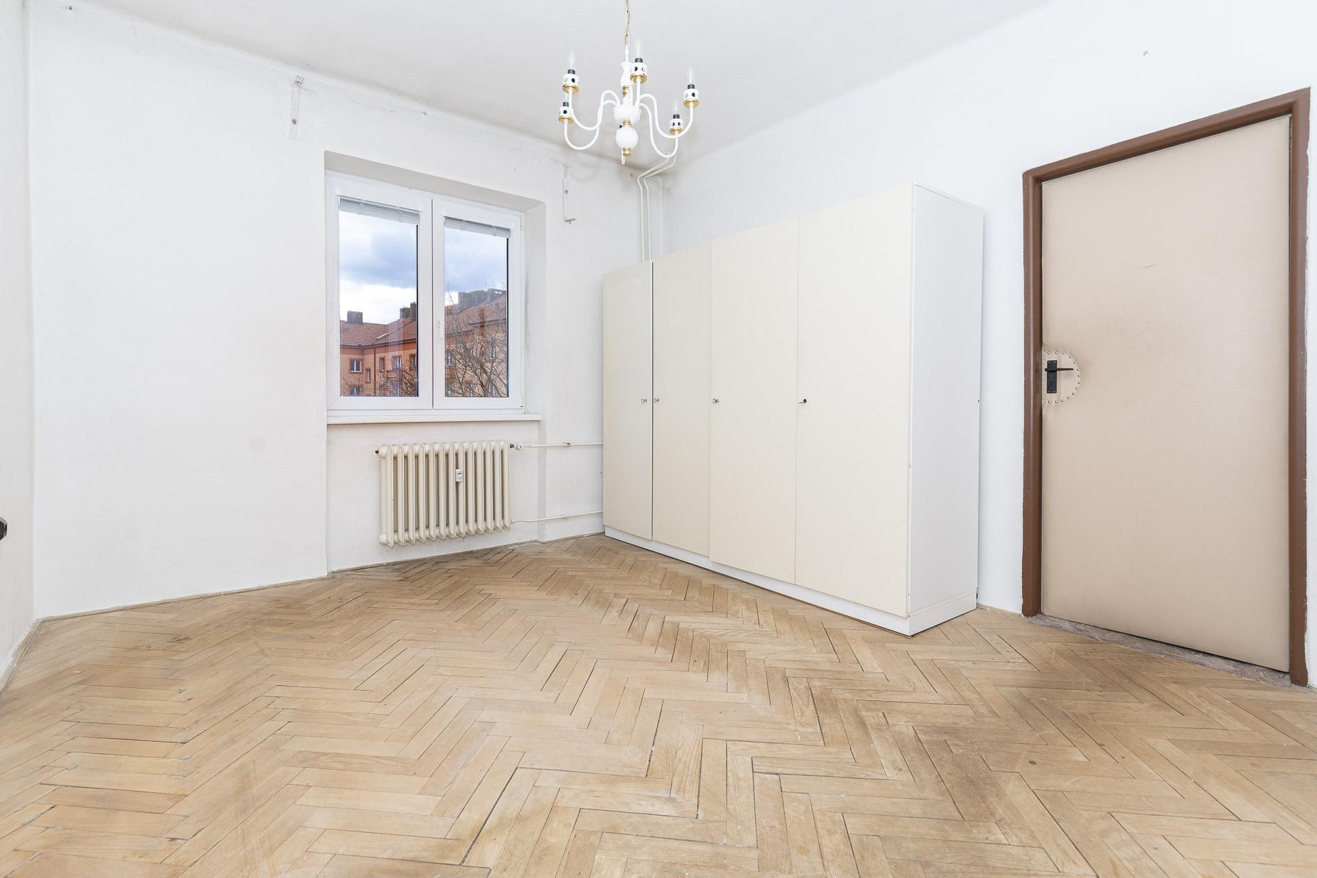 ložnoce s dřevěnou podlahou a dveřmi